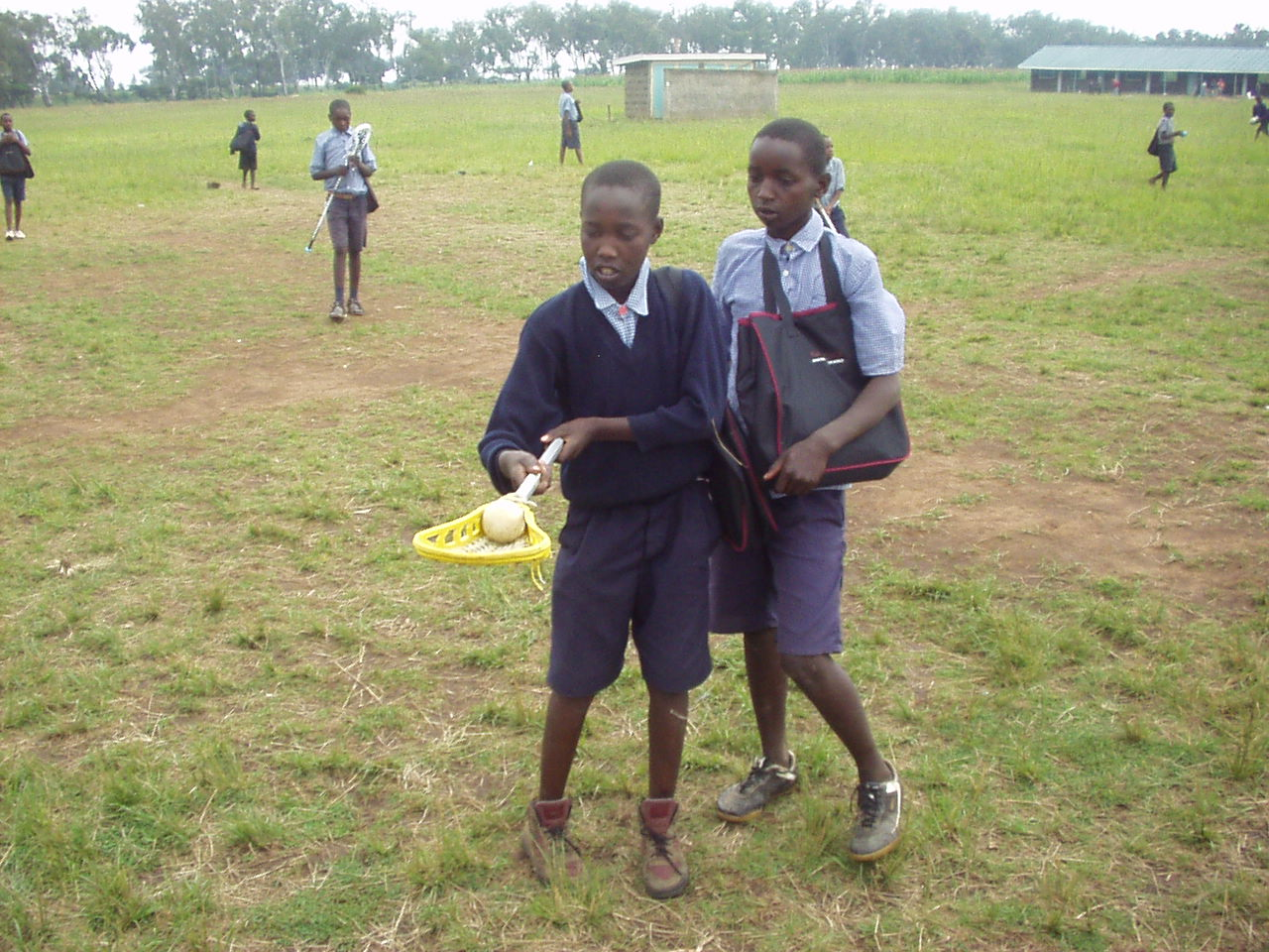 Two Kenyan students looking at a lacrosse stick donated by World teacher aid