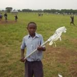 Kenyan student holding lacrosse stick donated by Charlie Lockwood of Gait/DeBeers Lacrosse
