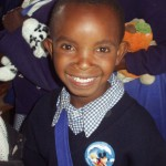 Smiling Kenyan boy after getting school supplies and donations from World Teacher Aid